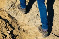 Plan rapproché des pieds du ` s de voyageur marchant vers le haut sur la montagne et le sable Photographie stock