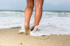 Plan rapproché des pieds nus du ` un s d'homme marchant à une plage, avec un ` s e de vague Images stock