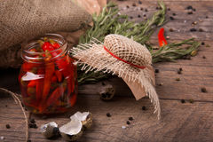 Plan rapproché des poivrons de piment épicés dans un pot, coquilles des oeufs de caille et romarin parfumé sur un fond en bois cl Photos libres de droits