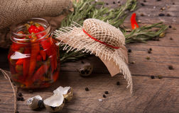 Plan rapproché des poivrons de piment épicés dans un pot, coquilles des oeufs de caille et romarin parfumé sur un fond en bois cl Photo libre de droits