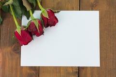 Plan rapproché des roses rouges sur un fond en bois avec le message vide Image libre de droits