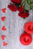 Plan rapproché des roses rouges sur un fond gris avec les coeurs et les bougies de papier, concept de vacances Images libres de droits