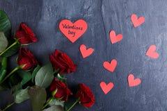 Plan rapproché des roses rouges sur un fond noir avec les coeurs de papier, concept de vacances Photo libre de droits