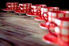 Plan rapproché des tasses rouges colorées de coffe sur la table en bois Photos stock