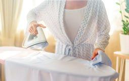 Plan rapproché des vêtements repassants de femme sur la planche à repasser photos libres de droits
