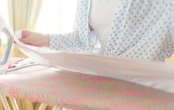 Plan rapproché des vêtements repassants de femme sur la planche à repasser photos stock