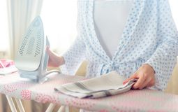 Plan rapproché des vêtements repassants de femme sur la planche à repasser images libres de droits
