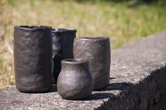 Plan rapproché des vases en céramique noirs faits main uniques à la lumière du soleil d'été avec différentes textures Photo libre de droits