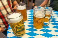 Plan rapproché des verres de bière bavarois bière de 1 litre sur le decoation de table chez l'Octoberfest photographie stock libre de droits