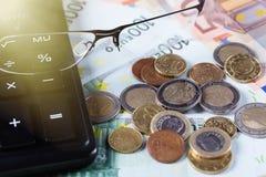 Plan rapproché des verres sur d'euro billets de banque avec les pièces de monnaie et la calculatrice Concept d'affaires Images libres de droits