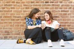 Plan rapproché Deux jeunes beaux amis de femmes à l'aide du comprimé numérique Photos stock