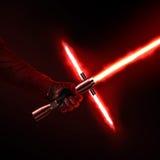 Plan rapproché disponible de nouveau de lumière rouge holdng de sabre d'isolement sur le noir Photo stock