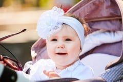 Plan rapproché du bébé drôle s'asseyant dans la poussette et les lunettes de soleil de prises photographie stock libre de droits