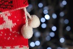 Plan rapproché du bas de Noël accrochant avec des lumières de Noël derrière Images stock