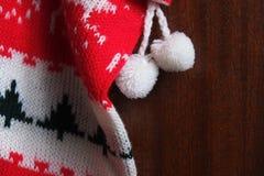 Plan rapproché du bas de Noël accrochant sur une porte en bois Photos stock