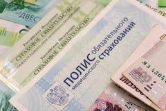 Plan rapproché du certificat d'assurance russe de politique d'assurance médicale maladie de l'argent de Fédération de Russie d'as photographie stock libre de droits