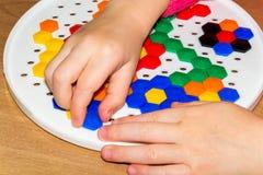 Plan rapproché du child& x27 ; mains de s prenant les pièces lumineuses de mosaïque apprenant des couleurs à la maison Photos libres de droits