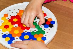 Plan rapproché du child& x27 ; mains de s prenant les pièces lumineuses de mosaïque apprenant des couleurs à la maison Photos stock