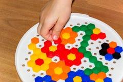 Plan rapproché du child& x27 ; mains de s prenant les pièces lumineuses de mosaïque apprenant des couleurs à la maison Images libres de droits