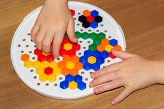 Plan rapproché du child& x27 ; mains de s prenant les pièces lumineuses de mosaïque apprenant des couleurs à la maison Image libre de droits
