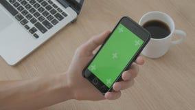 Plan rapproché du contact masculin de mains du smartphone sur le lieu de travail sur le fond en bois de table Clé verte de chroma clips vidéos