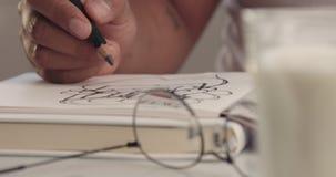 Plan rapproché du dessin de main du ` s d'homme de métis en bloc-notes banque de vidéos