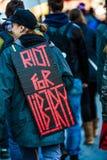 Plan rapproché du dos d'un protestataire portant un signe indiquant l'émeute pour la liberté Image stock