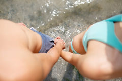 Plan rapproché du garçon et de la fille tenant des mains sur le fond de plage Jeunes ami et amie Concept roman adolescent Photos stock