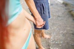 Plan rapproché du garçon et de la fille tenant des mains sur le fond de plage Jeunes ami et amie Concept roman adolescent Images stock