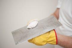 Grattoir et travailleur à la maison remplissant de rénovation Images stock
