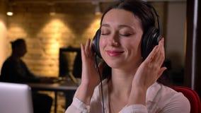 Plan rapproché du jeune employé de bureau féminin gai écoutant la musique avec ses mains sur les écouteurs souriant et regardant banque de vidéos