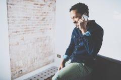 Plan rapproché du jeune homme africain barbu faisant la conversation avec des amis sur le smartphone au siège social moderne Pers Images libres de droits