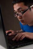 Plan rapproché du jeune homme asiatique travaillant sur l'ordinateur portatif Photographie stock libre de droits
