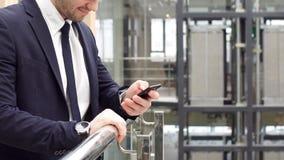 Plan rapproché du jeune homme d'affaires de main à l'aide d'un smartphone dans le bureau moderne banque de vidéos
