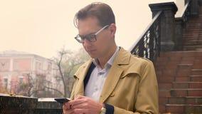 Plan rapproché du mâle caucasien attirant dactylographiant au téléphone se tenant calmement en parc dehors banque de vidéos
