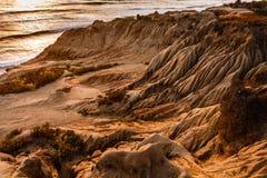 Plan rapproché du modèle de l'érosion des falaises de côté d'océan au coucher du soleil images libres de droits