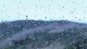 Plan rapproché du mouvement de gouttelettes d'eau sur le verre avec la tache floue de Mountain View et la pluie à l'arrière-plan clips vidéos