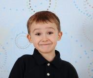 Plan rapproché du petit garçon doux effectuant un sourire mignon Photographie stock