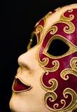 Plan rapproché du rouge et du masque de carnaval d'or sur le noir Images libres de droits
