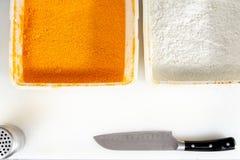 Plan rapproché du roulement vers le haut des sushi sur la cuisine avec le couteau et les ingrédients images stock