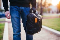 Plan rapproché du sac tenu par la main enfilée de gants du voleur Photographie stock libre de droits