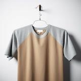 Plan rapproché du T-shirt multicolore vide de coton accrochant dans le mur en béton vide central Maquette claire de label avec fo Images stock