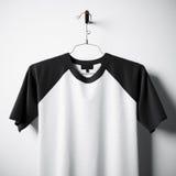 Plan rapproché du T-shirt noir et blanc vide de coton accrochant dans le mur en béton vide central Maquette claire de label avec  Photos stock