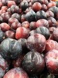 Plan rapproché du tas des prunes rouges et pourpres organiques fraîches Image stock