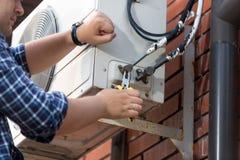 Plan rapproché du technicien masculin réparant le climatiseur extérieur uni Photo stock