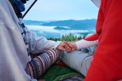 Plan rapproché du type et de la fille tenant des mains se reposant dans la tente sur les montagnes brouillées de fond Image stock