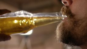 Plan rapproch? du visage d'un homme avec une moustache et une bi?re blonde potable de barbe d'une bouteille vid?o 4K banque de vidéos