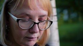 Plan rapproché du visage d'une fille avec des verres qui regarde soigneusement le livre La fille se tient près d'un arbre en parc clips vidéos