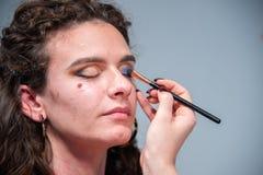 Plan rapproché du visage d'une fille tout en étant mis sur le maquillage par un artiste de maquillage professionnel photographie stock libre de droits