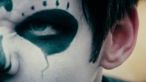 Plan rapproché du visage masculin avec le maquillage effrayant de zombi, acteur posant devant l'appareil-photo banque de vidéos